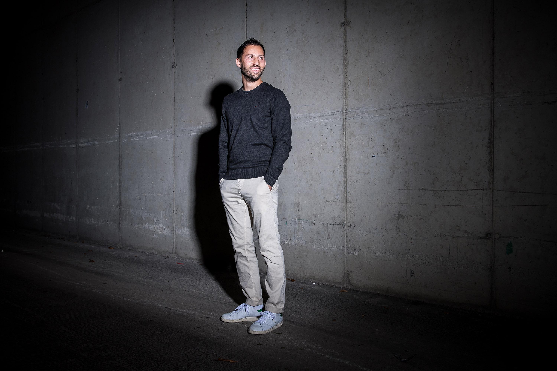 Schalkes Trainer Domenico Tedesco steht vor einer Mauer und wirft einen Schatten auf die Wand. Werbeshooting durch geführt von der Werbeagentur Medien Formen Werte aus Münster