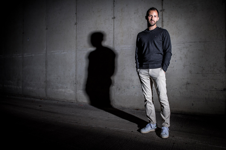 Schalkes Trainer Domenico Tedesco steht vor einer Mauer und wirft einen Schatten auf die Wand. Werbeshooting durchgeführt von der Werbeagentur Medien Formen Werte aus Münster