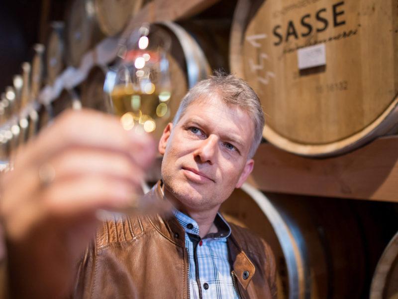 Rüdiger Sasse von der Sasse Feinbrennerei steht zwischen alten Holzfässern und nimmt eine Probe Lagerkorn in Augenschein. Werbeshooting durchgeführt von der Werbeagentur Medien Formen Werte aus Münster