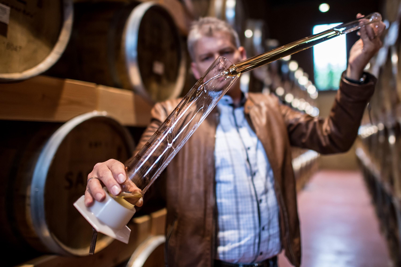 Rüdiger Sasse von der Sasse Feinbrennerei steht zwischen alten Holzfässern und füllt eine Probe Lagerkorn in ein Glasgefaeß. Werbeshooting durchgeführt von der Werbeagentur Medien Formen Werte aus Münster