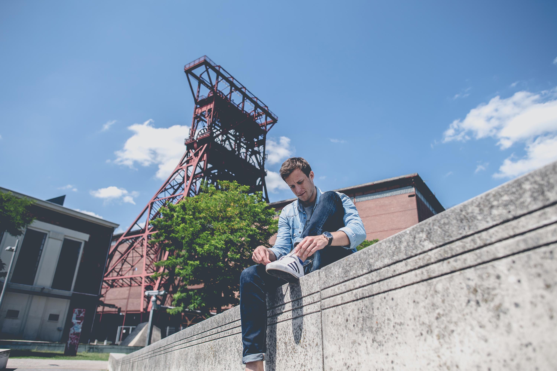 Mann sitzt auf Mauer bei einem Katalog Fotoshooting für den FC Schalke 04, durchgeführt von der Werbeagentur Medien Formate Werte aus Münster