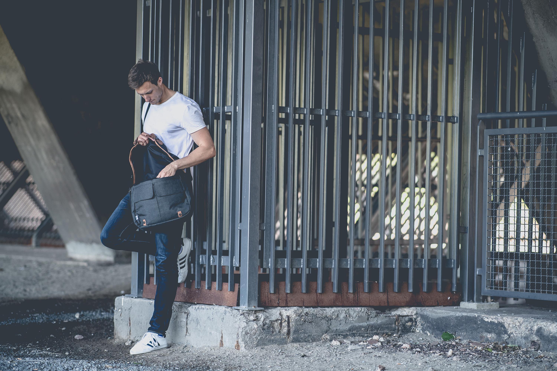 Mann lehnt mit seiner Tasche am Zaun bei einem Katalog Fotoshooting für den FC Schalke 04, durchgeführt von der Werbeagentur Medien Formate Werte aus Münster
