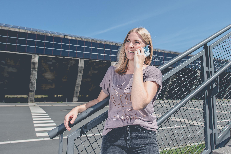 Frau telefoniert bei einem Katalog Fotoshooting für den FC Schalke 04, durchgeführt von der Werbeagentur Medien Formate Werte aus Münster
