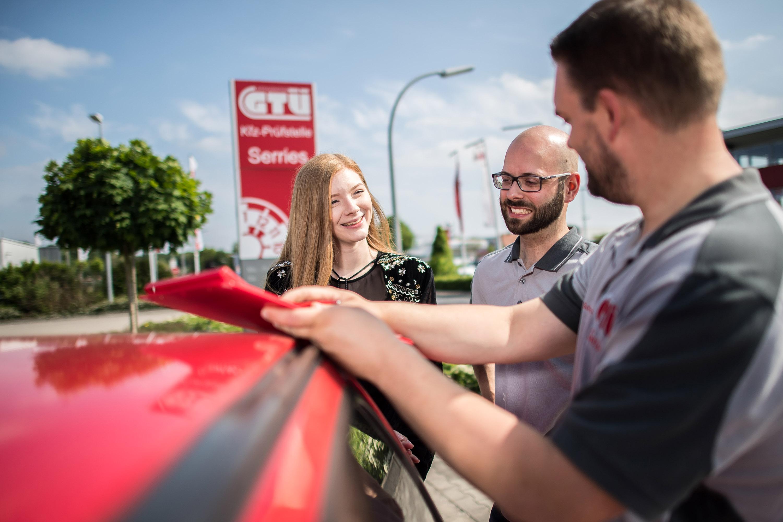 Mitarbeiter der GTÜ Warendorf mit Kundin am Auto. Das Werbeshooting wurde von der Werbeagentur Medien Formen Werte aus Münster durchgeführt.