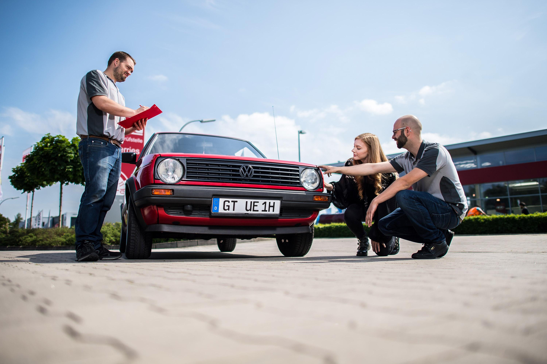 Mitarbeiter der GTÜ Warendorf mit Kundin vor Auto. Das Werbeshooting wurde von der Werbeagentur Medien Formen Werte aus Münster durchgeführt.