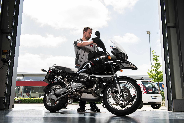 Mitarbeiter der GTÜ Warendorf steht mit Motorrad in der Einfahrt. Das Werbeshooting wurde von der Werbeagentur Medien Formen Werte aus Münster durchgeführt.