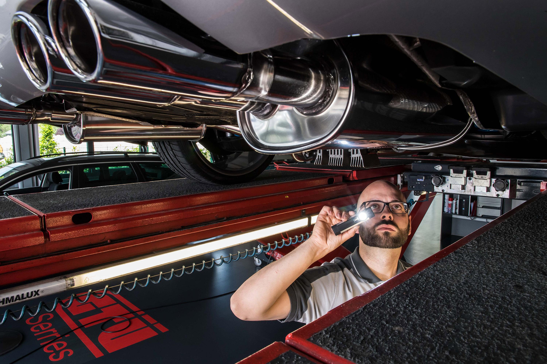 Mitarbeiter leuchtet von unten an das Auto bei einem Werbeshooting für die GTÜ Warendorf. Durchgeführt von der Werbeagentur Medien Formen Werte aus Münster