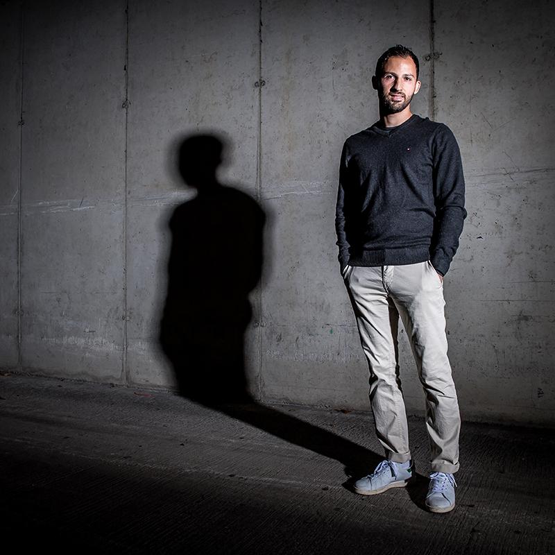 Schalkes Trainer Domenico Tedesco steht vor einer Mauer und wirft einen Schatten auf die Wand. Das Werbeshooting wurde von der Werbeagentur Medien Formen Werte aus Münster durchgeführt.